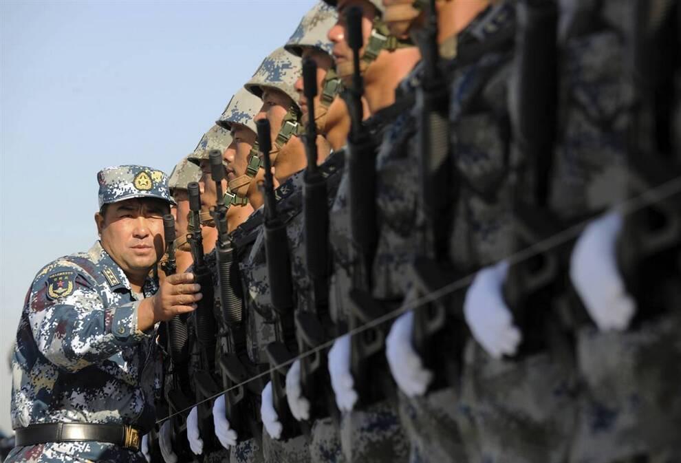 6) Инструктор выравнивает строй военных Народно-освободительной армии во время учебного марша на окраине Пекина 15 сентября. Во время репетиций парада посвященного этому значительному событию, были также отработаны полеты самолетов и вертолетов, выпускающих потоки красного, синего и желтого дыма. (Joe Chan/Reuters)