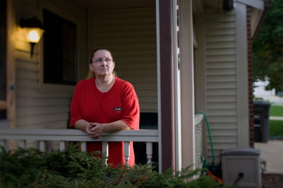 8. Джанет Берриер стоит у своего дома 23 сентября. Она готова съехать, как только придет уведомление, если ей не смягчат условия ипотеки. «Я уже упаковала большую часть вещей, - говорит она. – Чтобы не тратить время и успеть съехать вовремя, когда придет будет нужно».  Берриер взяла ипотеку в 2006 году и говорит, что считала проценты устоявшимися. Два года спустя ежемесячные выплаты увеличились на 200 долларов, а на работе она потеряла свои сверхурочные, за которые неплохо платили.  «Я могу оплатить половину ипотеки, - сказала она своему банку. – А они сказали, что этого недостаточно». (James Cheng/msnbc.com)