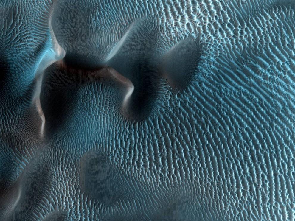 8. На этом снимке, сделанном станцией «Mars Reconnaissance Orbiter» и опубликованном 7 октября, видно, как марсианские ветры придают песку причудливую форму. Снимок представлен не в красных, а в голубых тонах, чтобы можно было различить малейшую разницу в композиции поверхности. (University of Arizona via NASA/JPL)