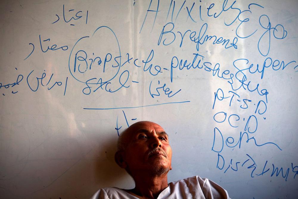 9) Пациент центра Али Хан, проходящий программу детоксикации, стоит, прислонившись к доске с записями в одном из классов в кабульском наркологическом центре 29 сентября. (Paula Bronstein/Getty Images)