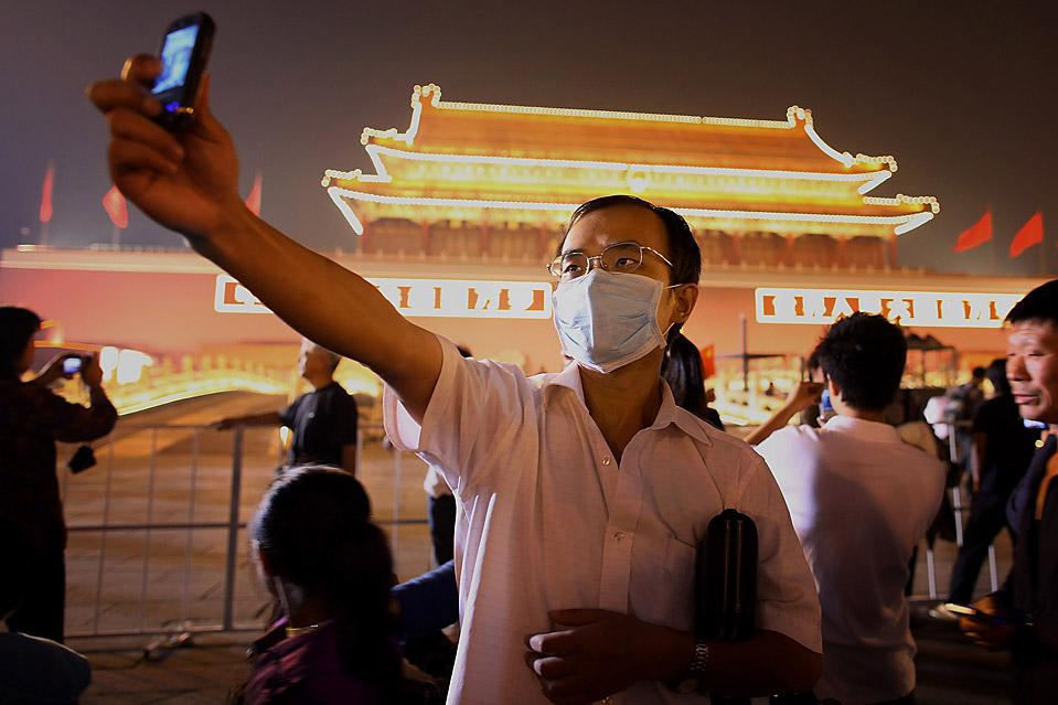 1) Мужчина фотографируется мобильным телефоном на фоне ворот Тяньаньмэнь в Пекине во вторник, накануне празднования 60-летия со дня основания Народной Республики Китай. (Feng Li/Getty Images)