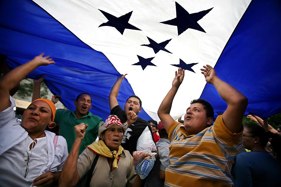 2) Люди под флагом Гондураса во время демонстрации в поддержку бывшего президента Мануэля Селайи, который был отстранен от власти в результате государственного переворота в июне. Снимок сделан в Тегусигальпе во вторник. (Rodrigo Abd/Associated Press)