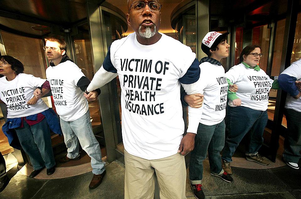 """5) Сторонники здоровоохранительной реформы образовали живую цепь в фойе здания в Нью-Йорке, где находится отделение страховой компании """"Этна"""". Нью-йоркская полиция, в конце концов, арестовала протестующих. (Mario Tama/Getty Images)"""