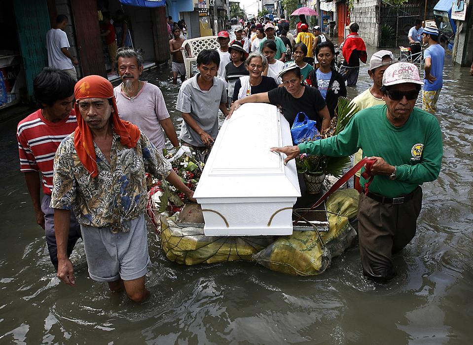 8) Скорбящие родственники везут тело на импровизированном плоту во время похоронной процессии городе Ризал на Филиппинах. Тайфун Кетцана унес более 300 жизней по всей Юго-Восточной Азии. (Romeo Ranoco/Reuters)