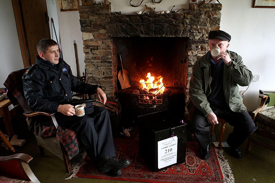 11) Работник избирательного пункта Хью O'Доннелл, справа, и офицер Брендан МакКан пьют чай во время доставки избирательных урн на остров Иннисфри в Ирландии. Ирландские избиратели придут на избирательные участки на второй референдум по Лиссабонскому договору ЕС. (Peter Morrison/Associated Press)