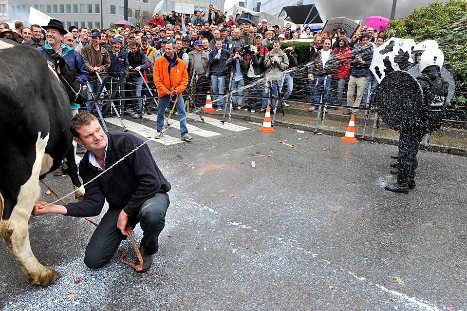 16) Фермер брызгает молоком в полицейских во время демонстрации против низких цен на молоко у здания штаб-квартиры ЕС в Брюсселе.  (Georges Gobet/AFP/Getty Images)