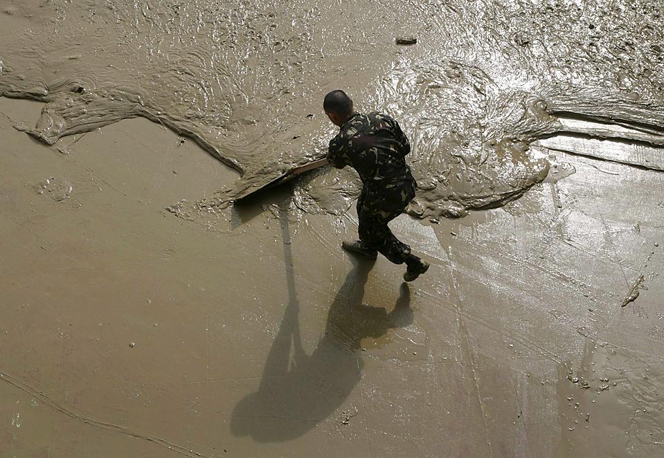 5) Солдат очищает от грязи школьный двор после наводнения в городе Марикина, в пригороде филиппинской столицы Манила. Тайфун Парма медленно прошел над северо-востоком Филиппин в воскресенье, в результате чего погибли 17 человек. (Cheryl Ravelo/Reuters)