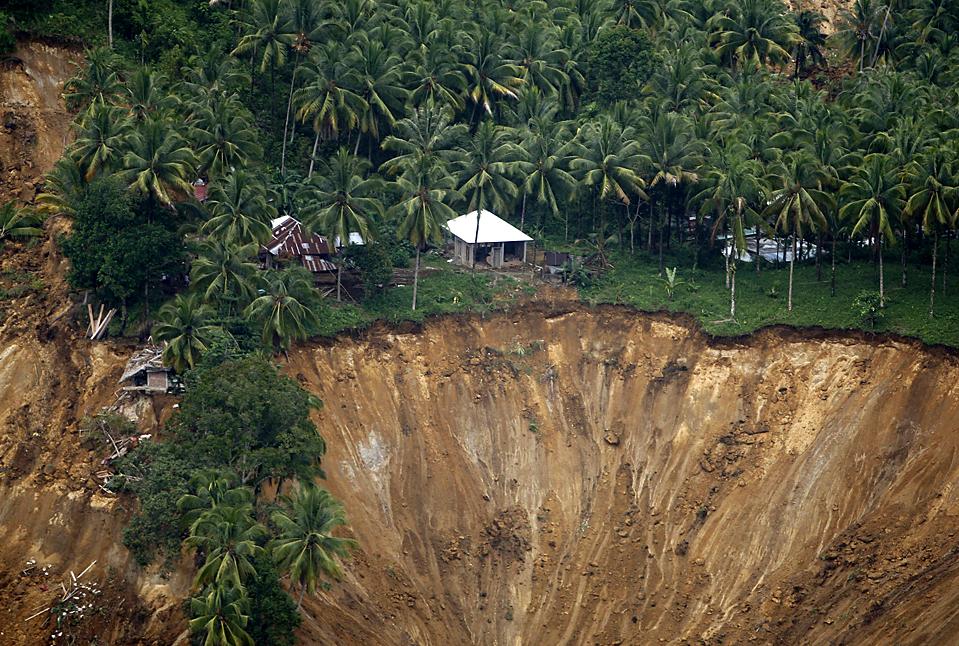 6) Дома разрушенные оползнями, которые вызвало землетрясение. Снимок сделан в отдаленной деревне Кота Тимур, в провинции Паданг, на индонезийском острове Суматра. (Dita Alangkara/Associated Press)