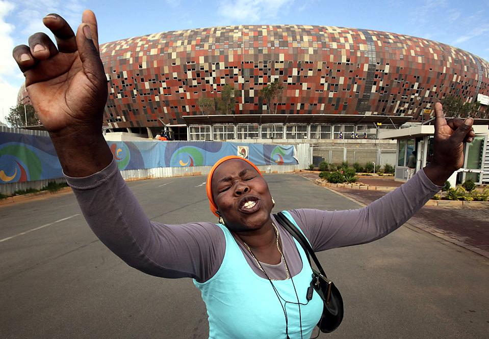 7) Софья Талагане, председатель неофициальной группы торговцев, снабжающих продовольствие строителей на стройплощадке городского футбольного стадиона, расположенной к югу от Йоханнесбурга, ЮАР, выступает против их выселения со стройплощадки. Трейдеры направили уведомление об освобождении помещений в пятницу, а в понедельник полиция приехала, чтобы изгнать рабочих. (Denis Farrell/Associated Press)