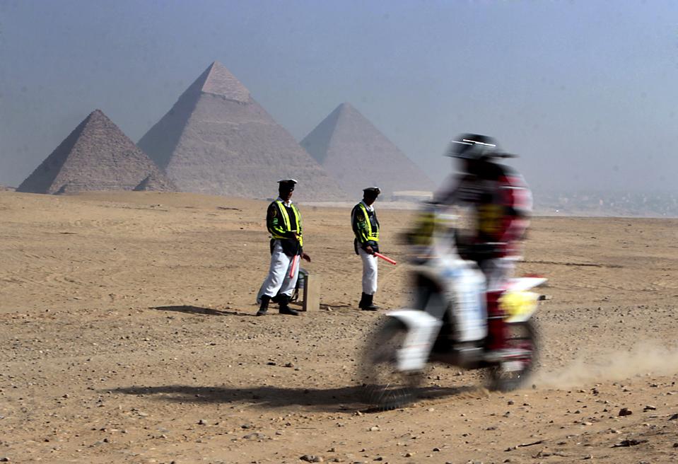 12) Египетская дорожная полиция наблюдает за падением с мотоцикла неизвестного спортсмена в начале 12-го Международного ралли по пересечённой местности на фоне пирамид Гизы в Египте. (Amr Nabil/Associated Press)