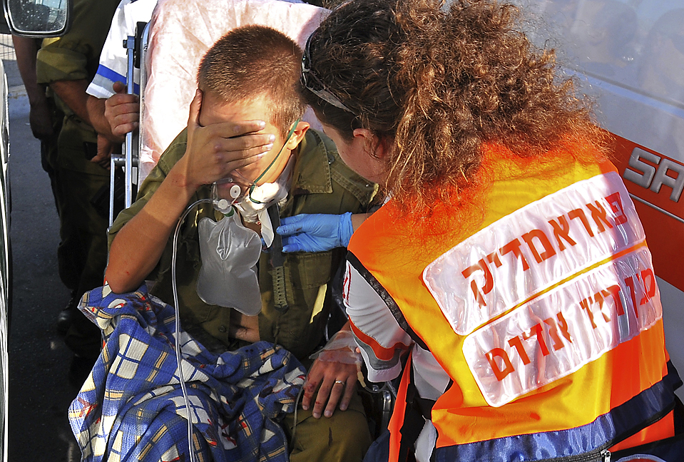 4) Медик фиксирует торчащий из шеи солдата нож в Иерусалиме. По данным полиции некто ударил ножом палестинского офицера на КПП, легко ранив его. Нападавший был задержан. (Guy Assayag/Associated Press)