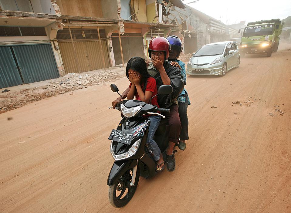 7) Семья едет по пыльной улице в Паданге, Индонезия. На прошлой неделе тут произошло землетрясение силой в 7,6-баллов, из-за которого погибли более 700 человек. (Dita Alangkara/Associated Press)