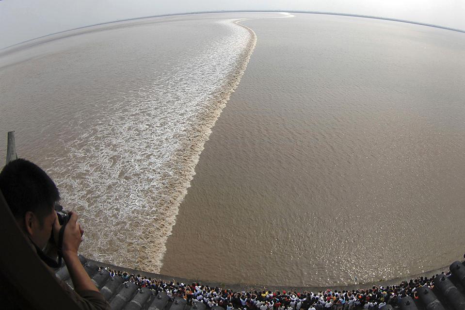 10) Люди смотрят на волну, стоя над рекой Цяньтан в Haining, провинция Чжэцзян, Китай. (Reuters)