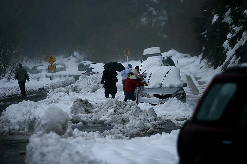 12) Водители возвращаются к своим автомобилям во время сильного снегопада около Napier в районе Хокс-Бей, в Новой Зеландии. Из-за сильнейшей метели сотни людей не могли вернуться домой. (Paul Тейлор/New Zealand Herald через Associated Press)