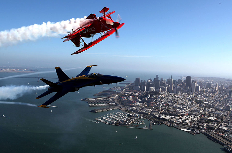12) Лётчик-ас Шон Такер, сверху и самолет ВМС США Blue Angels F/A-18 Hornet пилотируемый летчиком из Корпуса морской пехоты США Натаном Миллером пролетают над Сан-Франциско во время репетиций перед авиашоу. (Justin Sullivan/Getty Images)