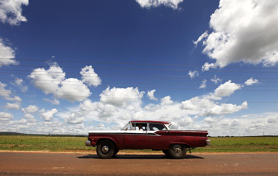3. Автомобиль проезжает мимо государственных земель недалеко от города Кивикан, Куба. На Кубе около 250 000 крестьянских семей и 1100 частных предприятий, которые совместно производят около 70% продовольствия в стране. (Desmond Boylan/Reuters)