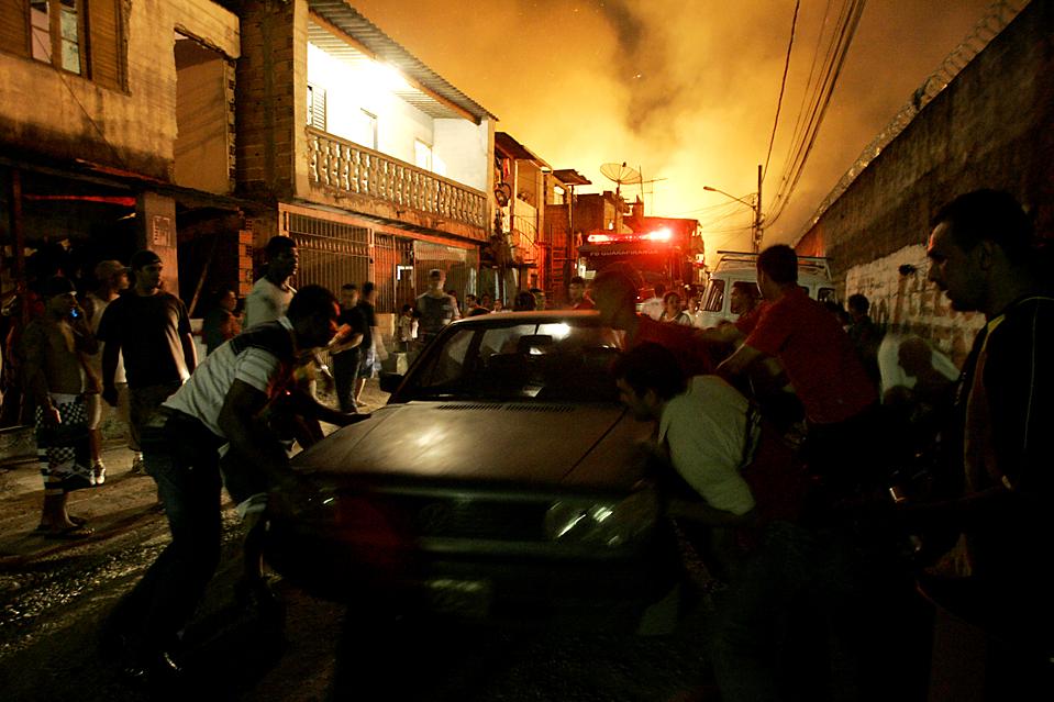 4. Люды пытаются спасти автомобиль после того, как в поселке Диого Пирес к западу от Сан-Паулу  разгорелся пожар. О летальных исходах не сообщалось, но двум людям потребовалась медицинская помощь. Причина пожара не установлена. (Nelson Antoine/Associated Press)