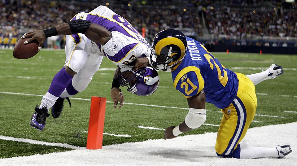 7. Игрок команды «Minnesota Vikings» Адриан Петерсон (слева) пересек зону защиты на 4-метровом тачдауне против защитника «St. Louis Rams» Ошиомого Атогве в матче в Сент-Луисе в воскресенье. «Vikings» выиграли со счетом 38-10. (Michael Conroy/Associated Press)