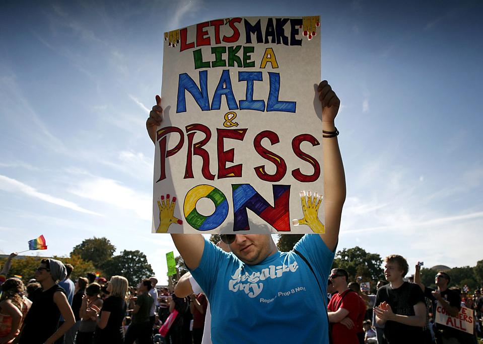 9. Мужчина держит плакат на митинге активистов выступающих за права геев, который прошел в Вашингтоне в воскресенье. В воздухе развивались тысячи радужных флагов, когда митингующие обратились с призывом к Бараку Обаме, чтобы тот сдержал обещание позволить геям служить в армии. «Эй, Обама, позволь мамочке жениться на мамочке», - скандировали люди. (Molly Riley/Reuters)
