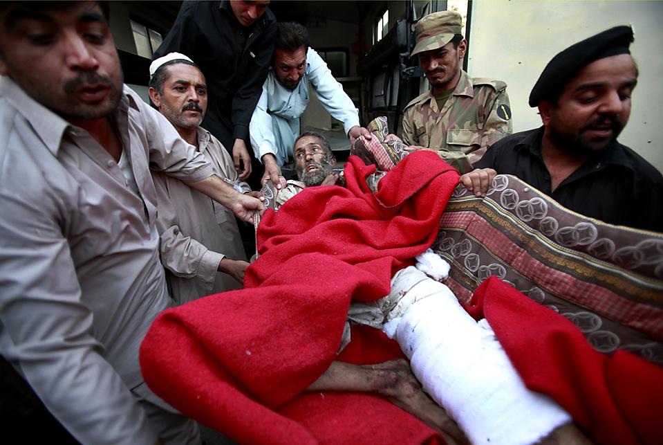 11. Раненого мужчину переносят в больницу в Пешаваре, Пакистан, в понедельник. Рядом с военным автомобилем на рынке в округе Шангла взорвался автомобиль террористов-смертников. В результате погиб 41 человек, включая 6 офицеров службы безопасности, а еще 45 получили ранения. (Fayaz Aziz/Reuters)