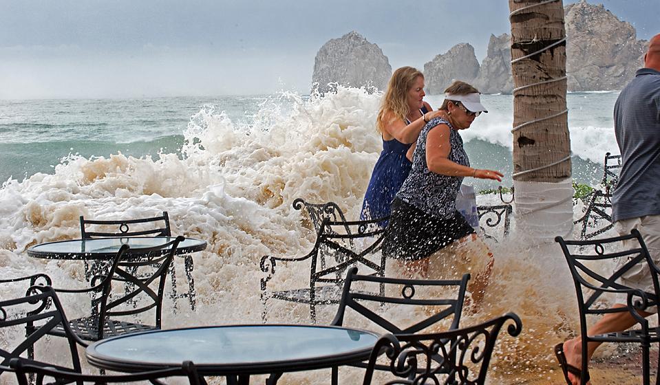 3) Люди, наблюдавшие за штормом, убегают с веранды гостиницы на пляже Медано в Кабо Сан Лукас, Мексика, после того, как большие волны от урагана Рик обрушились на берег. Скорость ветра внутри урагана достигает 165 километров в час. Его центр располагается в 340 километрах к югу от курортного города Кабо-Сан-Лукас. (Paul J. Richards/Agence France-Presse/Getty Images)