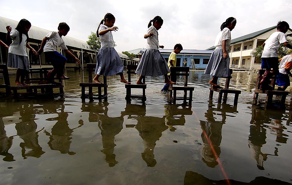 """4) Дети с помощью стульев переходят затопленный школьный двор в городе Тайтай, провинция Ризал на Филиппинах. Власти Филиппин готовятся к приходу тайфуна """"Лупит"""", спасательные службы страны, оснащенные вертолетами и специальными лодками, находятся в состоянии повышенной готовности. Ожидается, что тайфун 23 октября либо достигнет севера страны, либо проследует в сторону Тайваня. Его скорость составляет 210 км в час. (Noel Celis/Agence France-Presse/Getty Images)"""