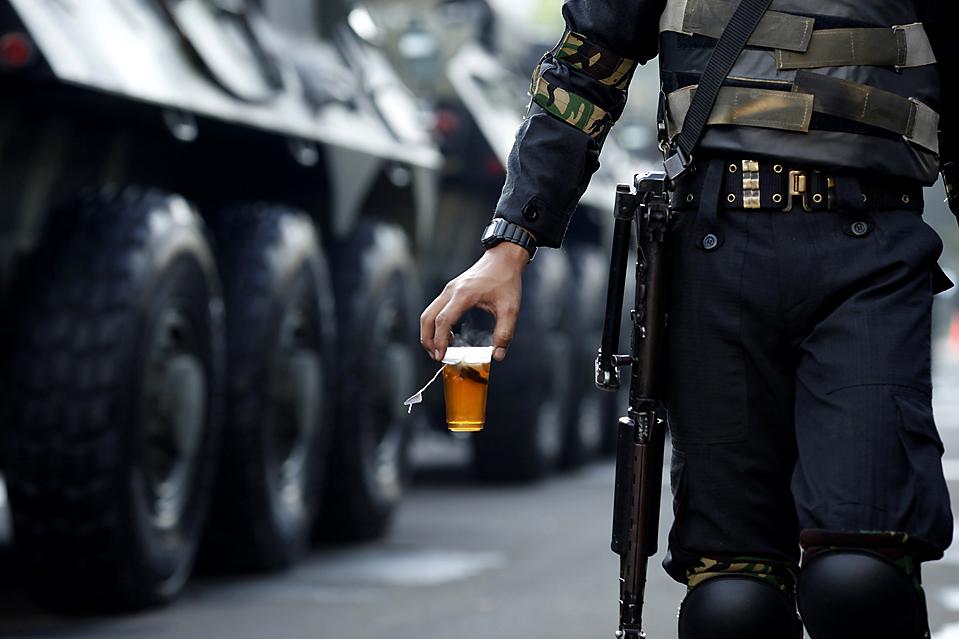 5) Солдат армии несет чай, проходя мимо бронированного автомобиля 60-летнего президента Сусило Бамбангом Юдхойоно, который был приведен к присяге на второй пятилетний срок в Джакарте, Индонезия. Отставной генерал с легкостью победил на выборах в июле. (Beawiharta/Reuters)