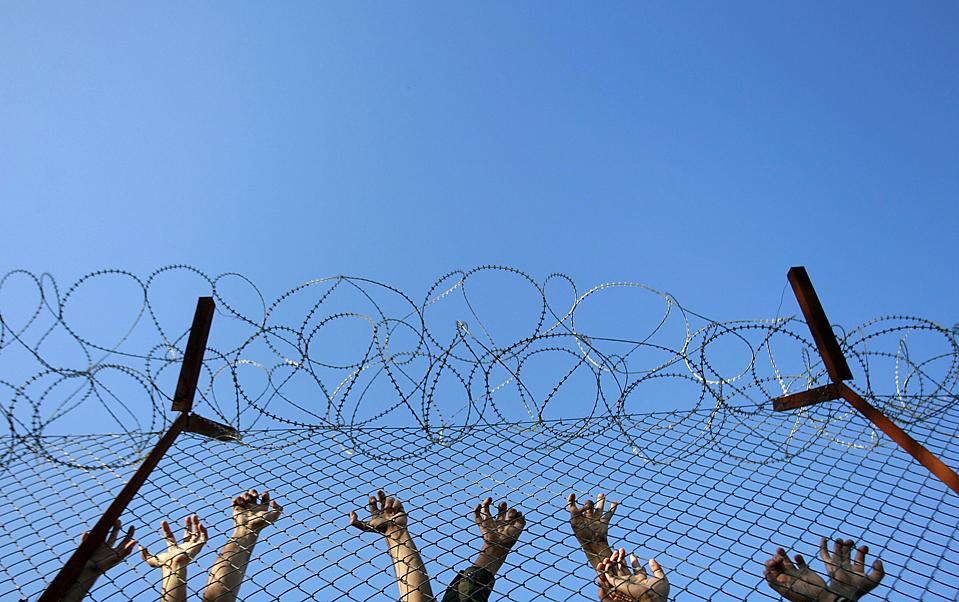 6) Иммигранты у забора во время беспорядков у центре содержания под стражей Pagani на греческом острове Лесбос. Около 800 человек находятся на этом объекте, который предназначен для содержания около 250 человек. (John Kolesidis/Reuters)