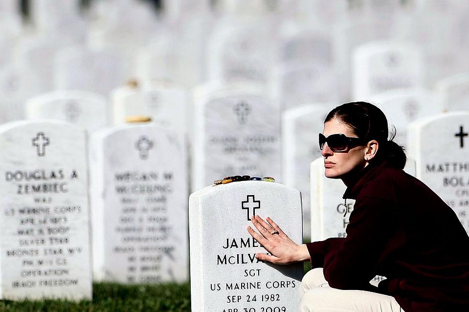 9) Шерил МакИлвэйна, вдова сержанта морской пехоты США. Джеймса МакИлвэйна, у его могилы на Арлингтонском Национальном кладбище, во время поминальной службы военного специалиста Стивена Мейса понедельник. Сержант МакИлвэйн был убит в Ираке в апреле, а Мейс был убит в Афганистане в октябре. (Win McNamee/Getty Images)
