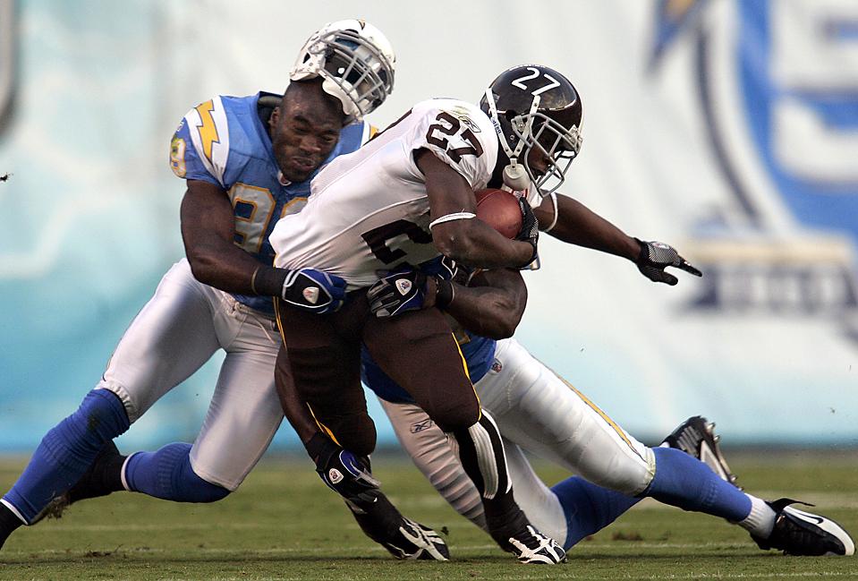 13) Полузащитник команды «San Diego Chargers» Кевин Бернетт и его партнер оттягивают игрока команды  «Denver Broncos» Кноушона Морена во время игры в Сан-Диего. «Broncos» выиграли со счетом 34-23. (Chris Park/Associated Press)
