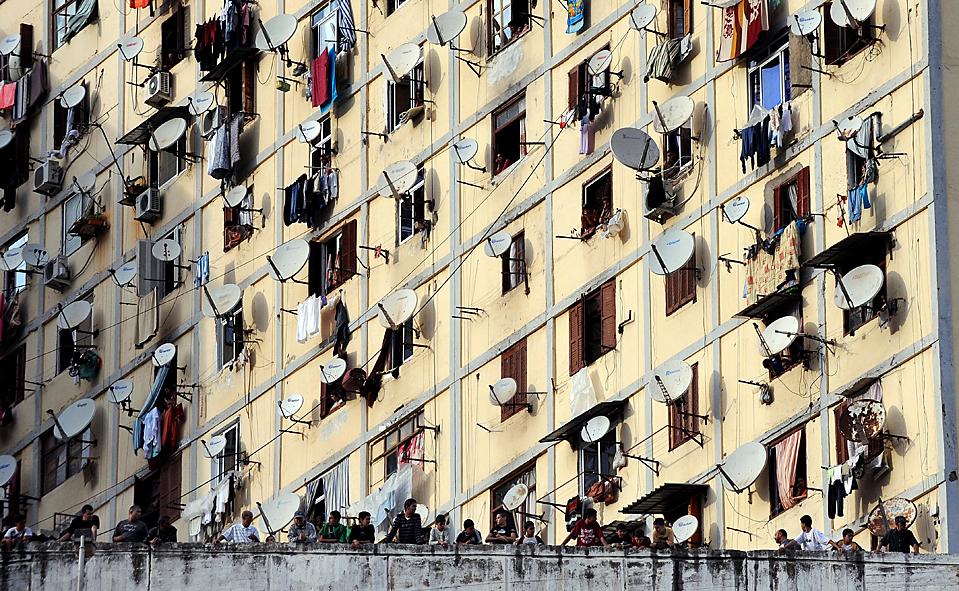 1. Жители наблюдают за столкновением в Алжире во вторник. Демонстранты швырялись камнями и газовыми бомбами в полицию, протестуя против безработицы и жилищного кризиса. Один офицер был серьезно ранен. Полиция использовала слезоточивый газ и бронетехнику, чтобы разогнать демонстрантов. (Fayez Nureldine/Agence France-Presse/Getty Images)