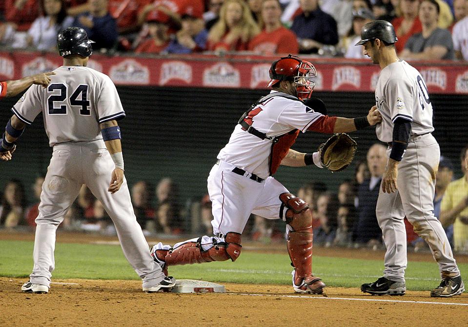 5. Майк Наполи из команды «Los Angeles Angel» отмечает Робинсона Кано и Джорджа Посада из «New York Yankees» во время четвертой игры Чемпионата Американской лиги в Анахейме, штат Калифорния, во вторник. «Yankees» выиграли со счетом 10-1 и повели в лиге с общим счетом 3-1. (Jae C. Hong/Associated Press)