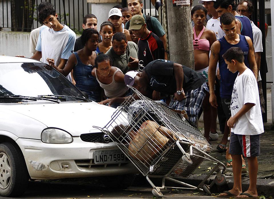 7. Жители смотрят на тело, найденное в тележке из супермаркета в Моро дос Макакос в Рио де Жанейро во вторник. Жители подозревают, что мужчину убили наркоторговцы из конкурирующих банд. Бразильский президент готов потратить на решение проблемы почти 60 миллионов долларов. (Ricardo Moraes/Reuters)