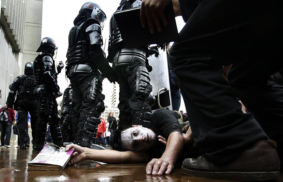 14. Студент университета лежит у ног полицейских штурмового отряда во время протеста против президента Альваро Урибе, требуя больше денег для общественных университетов в Боготе, Колумбия, во вторник. (Fernando Vergara/Associated Press)