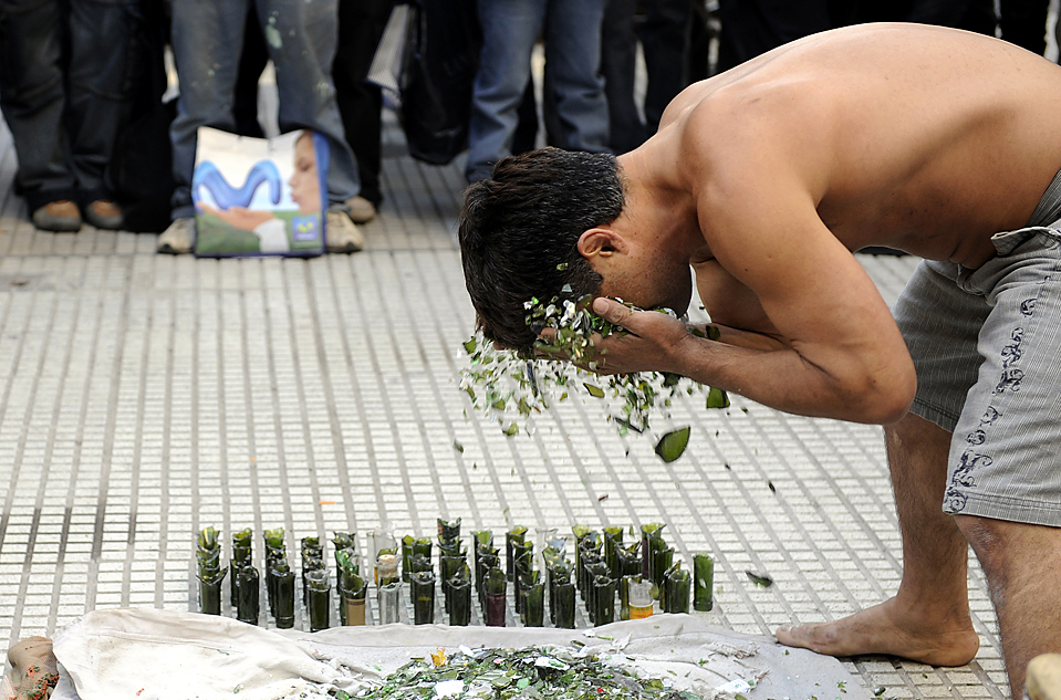 15. 34-летний бразилец Маркос Антонио да Луц «умывает» лицо битым стеклом на своем представлении в Буэнос-Айресе во вторник. (Daniel Garcia/Agence France-Presse/Getty Images)