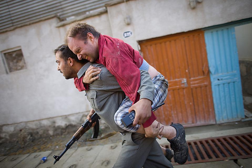 9. Немца со сломанной ногой несут в безопасное место после того, как в Кабуле боевики напали на международный пансион, убив 11 человек. (Paula Bronstein /Getty Images)