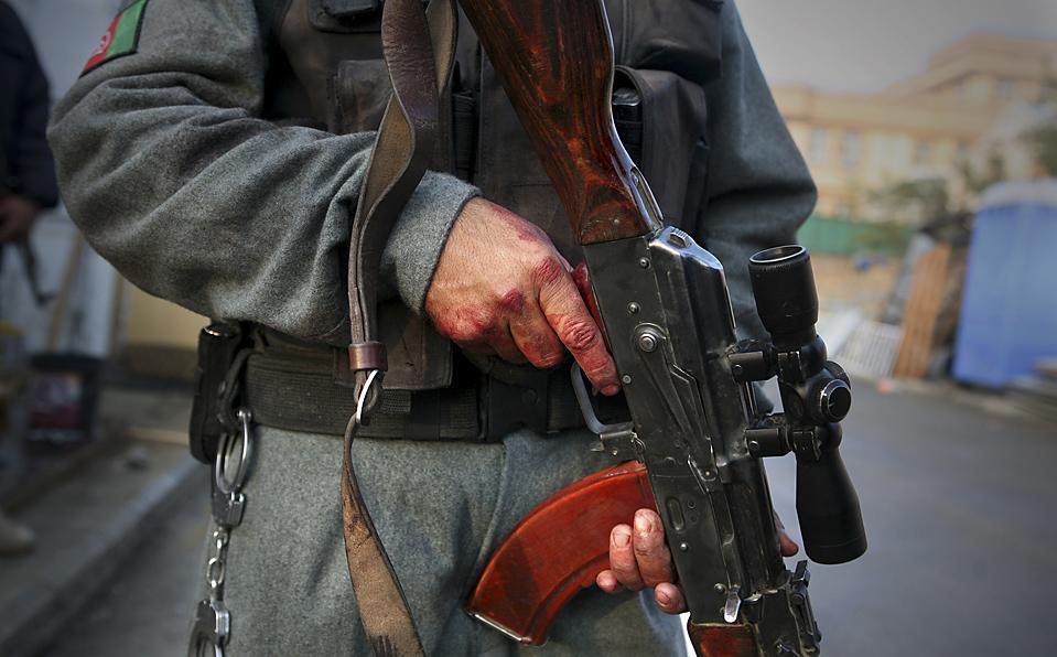 10. Окровавленные руки офицера полиции держат автомат после атаки на международный пансион в Кабуле. Боевики «Талибана» организовали атаки в Афганистане и Пакистане, убив, по меньшей мере, 100 человек. И все это в первый же день визита в регион госсекретаря США Хиллари Клинтон. (Altaf Qadri/Associated Press)