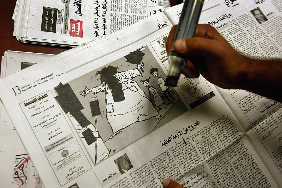 11. Арабский переводчик накладывает цензуру на картинки и статьи в газете, которую потом будут читать заключенные в Гуантанамо Бэй. (John Moore/Getty Images)