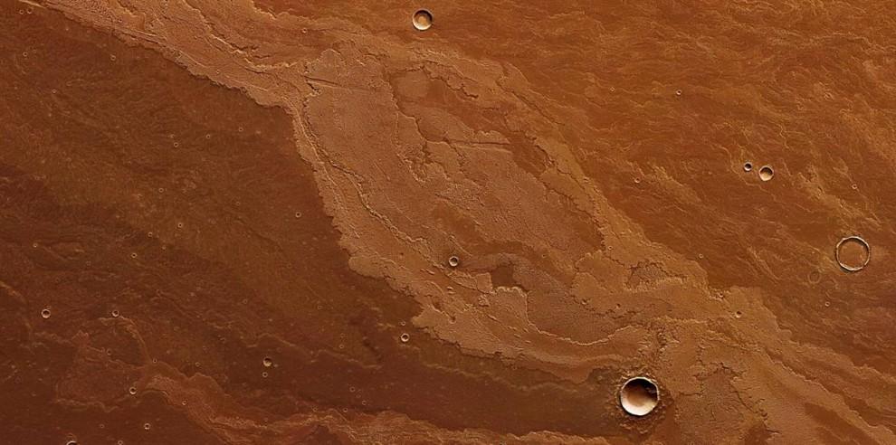 12. За всю геологическую историю Марса вулканическая лава стремительно бежит по региону, известному, как Равнина Дедалия, к юго-востоку от большого вулкана, известного под названием гора Арсия. На этом снимке, сделанном Европейской южной обсерваторией в Чили и опубликованном 9 октября, вы видите следы, оставленные огненными потоками. (ESA/DLR/FU Berlin)