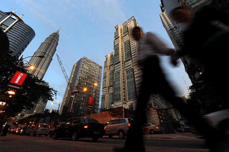 14) Офисные работники проходят на фоне небоскребов в центре Куала-Лумпура.