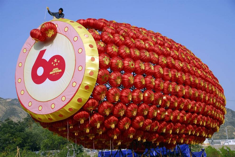 14) Рабочий заканчивает установку гигантского барабана из декоративных фонарей. (Reuters)