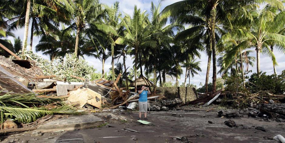 17) Гражданка США Хитер Пеннер, сотрудница «Coconut Resort» в Maninoa Siumu на южном побережье фотографирует последствия цунами,  уничтожившего курортный комплекс, в котором она работала.
