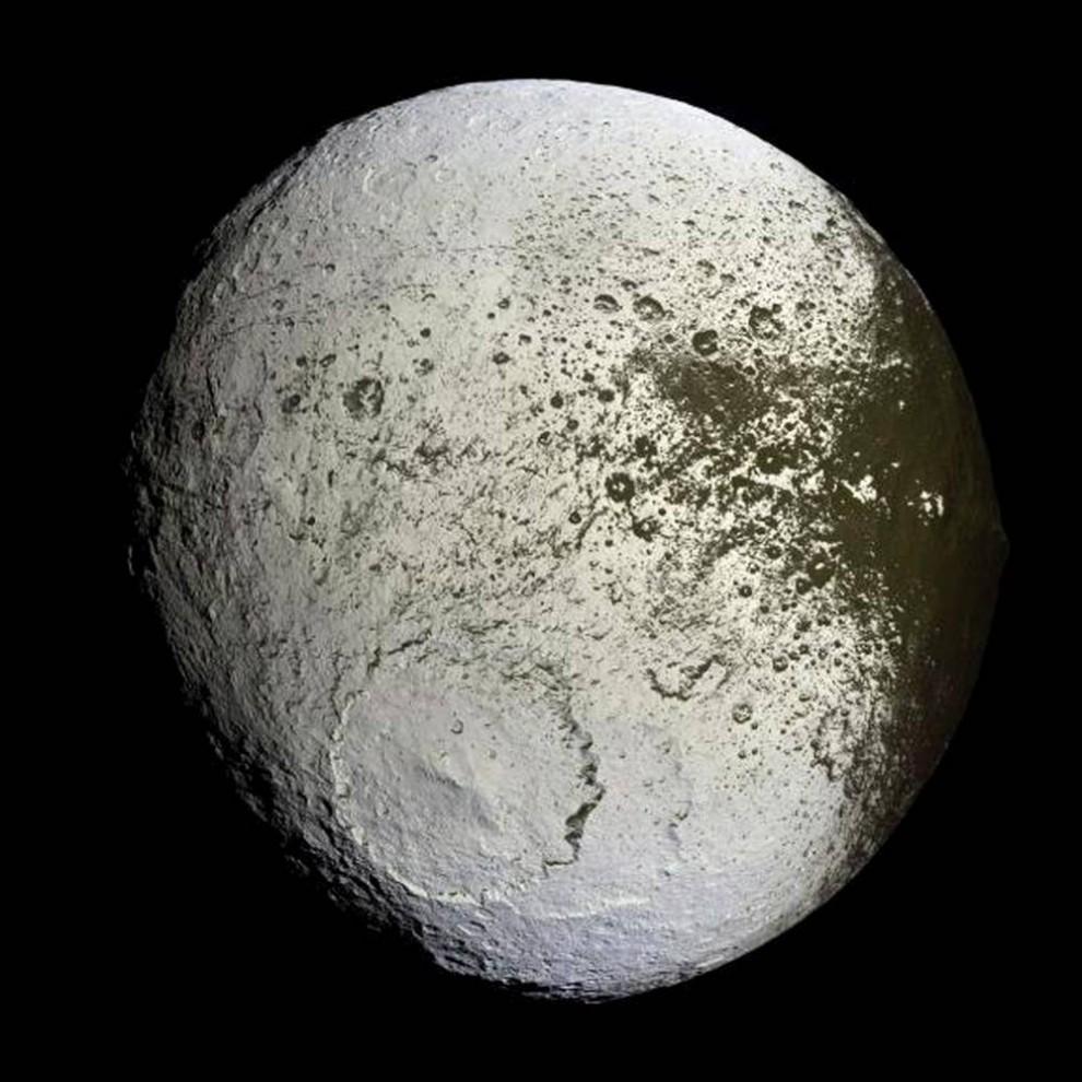 17. Темная пыль обволакивает половину естественного спутника Сатурна под названием Япет на этом снимке, сделанном летательным аппаратом «Кассини» в сентябре 2007 года. В издании «Nature» за 8 октября исследователи предположили, что источник пыли был почти невидимым кольцом обломков, отколовшихся от другого спутника – Фебы. Кольца начинаются примерно в 3,7 миллионах миль от Сатурна и тянутся на 7,4 миллионов миль. (EPA)