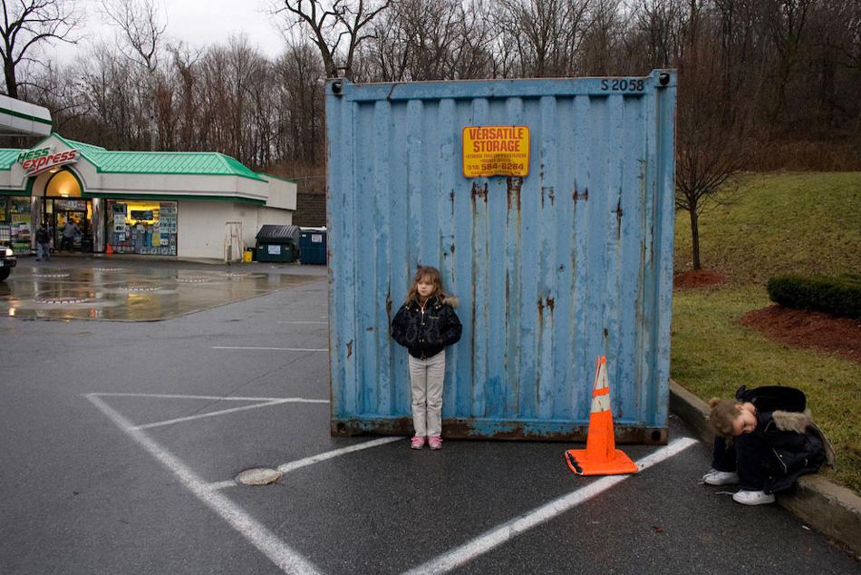 18) Две младшие дочери Дианы ждут свою мать у минимарта на заправочной станции, где она работает посменно. Половину своего заработка, Диана выплачивает в виде алиментов на детей.