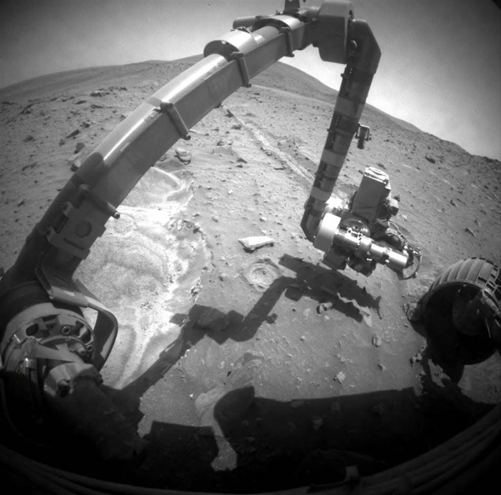 18. На этом снимке, сделанном 11 октября, ровер NASA «Spirit» вытягивает свою механическую «руку» для получения пробы с поверхности Марса. Яркая почва слева на фотографии представляет собой вязкое вещество, в котором ровер «увяз» на последние полгода. (Caltech / NASA via JPL)
