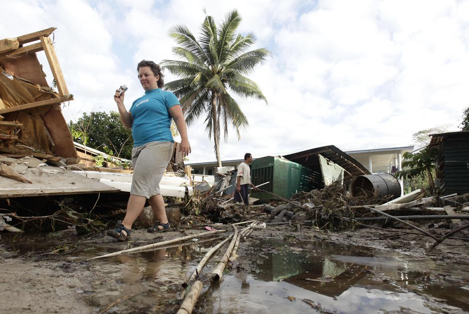 19) Гражданка США Хитер Пеннер, сотрудница «Coconut Resort» в Maninoa Siumu на южном побережье проходит мимо разрушенного цунами курортный комплекс, в котором она работала.
