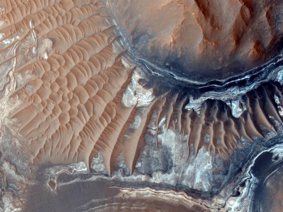 20. Залежи светлого вещества на песчаных дюнах на Марсе в регионе, известном, как Лабиринт ночи (Noctis Labyrinthus). Этот снимок был сделан с помощью фотоаппарата высоко разрешения на станции Mars Reconnaissance Orbiter. Данные с другого инструмента (CRISM) дают основания предполагать, что это вещество содержит железосодержащие сульфаты и глину. Фото было опубликовано 7 октября. (University of Arizona via NASA/JPL)