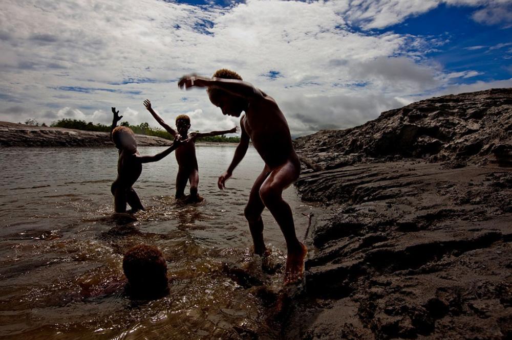 27. Дети из местного поселка играют в реке Ок Теди, окруженной токсичными осадочными породами, которые сбрасывались в реку из шахты в Киунга, Папуа — Новая Гвинея. Река Ок Теди также заметно высохла из-за этих выбросов. Ученые предсказали, что во время следующего наводнения река может отравить земли местных поселений, в которых проживает около 30 000 человек. (Brent Stirton/Getty Images)
