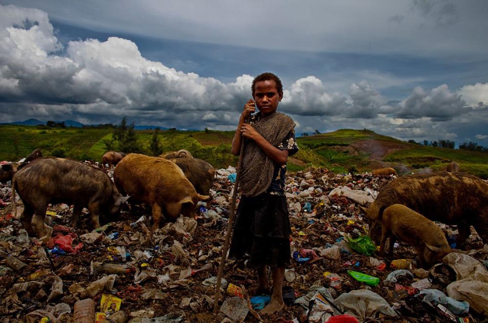 29. Мальчик стоит на свалке в Маунт Хаген, где живут те, кто переехал в город в 1970-ых и использовал свалку, чтобы выращивать свиней. Это довольно прибыльное занятие в Папуа — Новой Гвинее. (Brent Stirton/Getty Images)