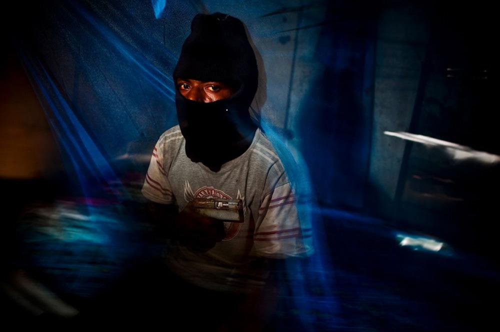 32. Член гангстерской группировки «Раскол» со сделанным вручную пистолетом. Снимок сделан в бедном поселении в 12 км от Порт-Морсби. (Brent Stirton/Getty Images)